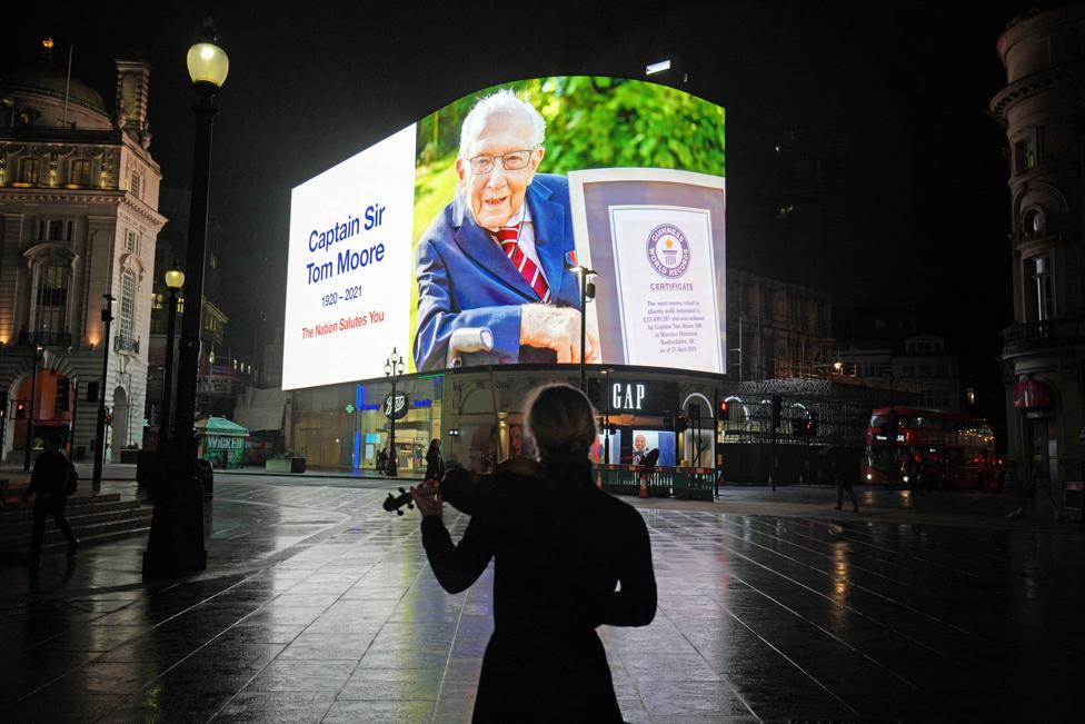 امرأة تعزف الفيولا ليلا بينما تتطلع إلى لافتة تطل على ميدان