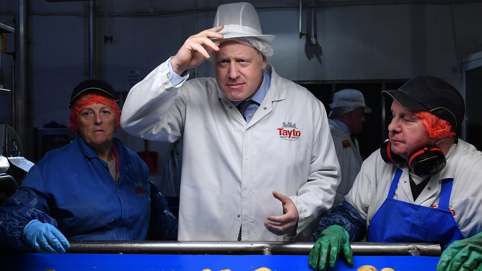 Boris Johnson on a visit to the Tayto factory, in a white jacket and workers hygiene hat