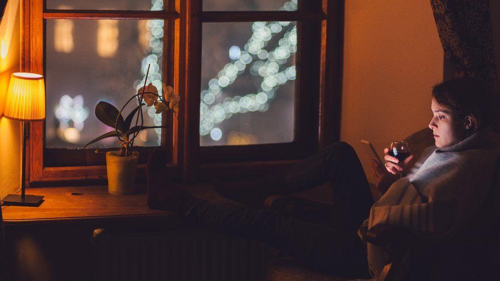 Mujer abrigada en un sofá tomando una copa de vino.