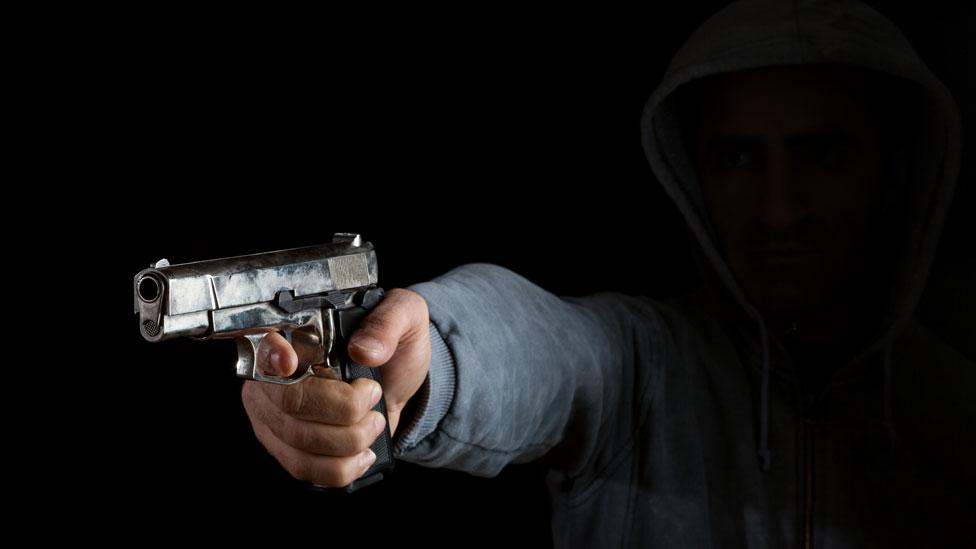 Hombre apuntando un arma.