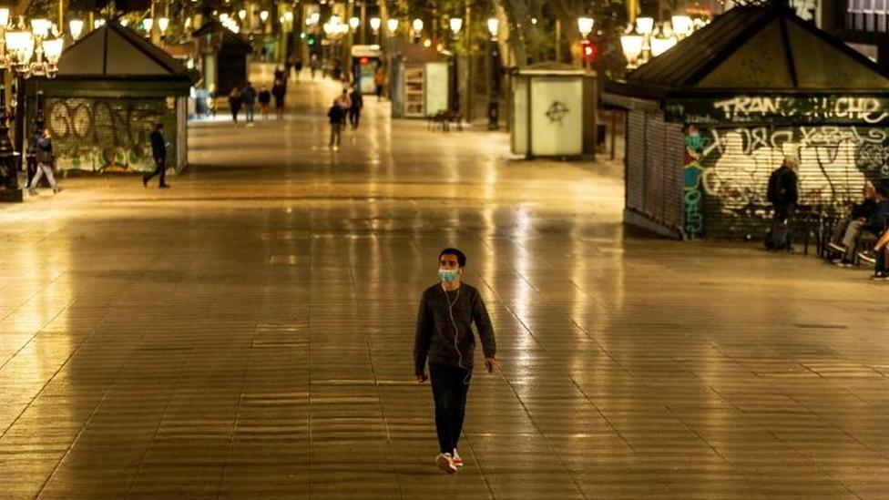 Homem de máscara caminha em rua de pedestres à noite