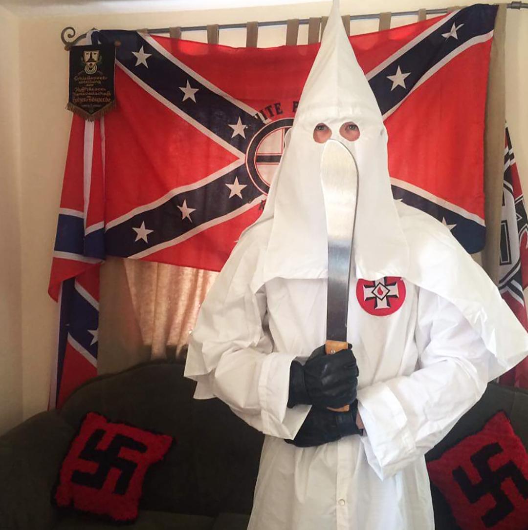 Thomas, en su casa, vestido con el atuendo del Ku Klux Klan y sosteniendo un machete.