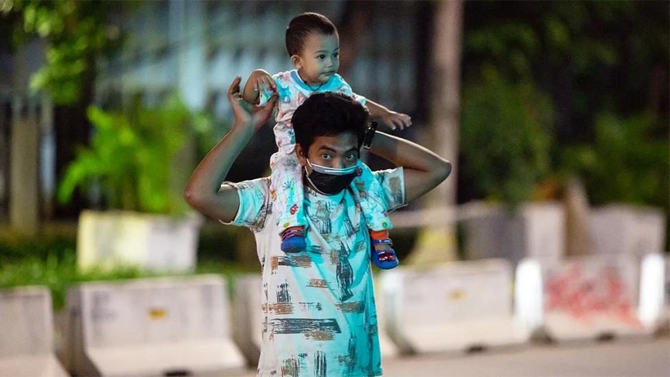 Un hombre asiático lleva sobre sus hombros a un pequeño