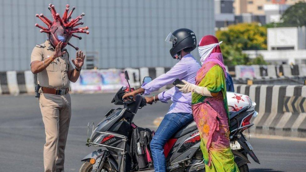 الشرطي راجيش بابو (يسار) يرتدي خوذة تحت عنوان فيروس كورونا ويتحدث إلى السائقين خلال إغلاق تفرضه الحكومة كإجراء وقائي ضد فيروس COVID-19 في تشيناي في 28 مارس/أذار 2020