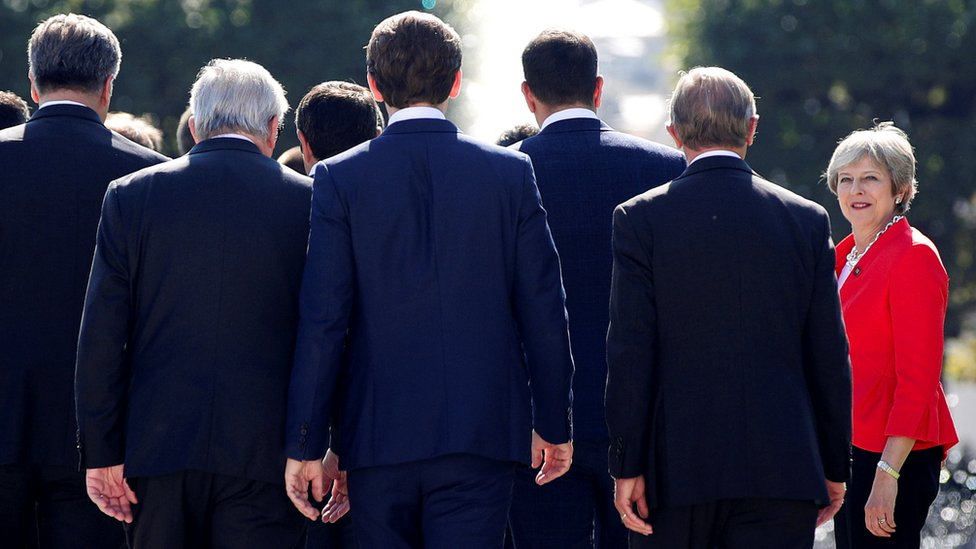 Theresa May, in red, faces the camera while EU leaders in dark suits walk away from the camera.