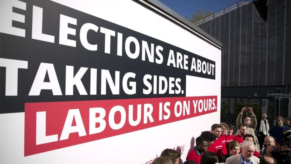 Jeremy Corbyn campaigning with Labour supporters in front of billboard saying: Elections are about taking sides. Labour is on yours.