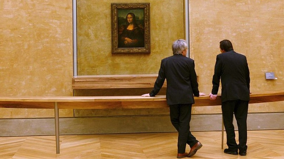 Two men look at the Mona Lisa at the Louvre Museum in Paris