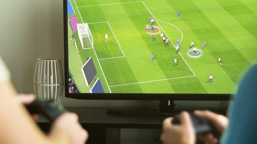 Una pantalla de televisión con un videojuego de fútbol y dos personas jugando.