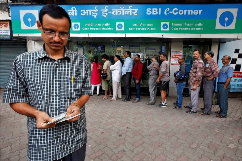A man counts Indian rupee banknotes after withdrawing them from State Bank of India ATM in Kolkata, India, November 11, 2016.