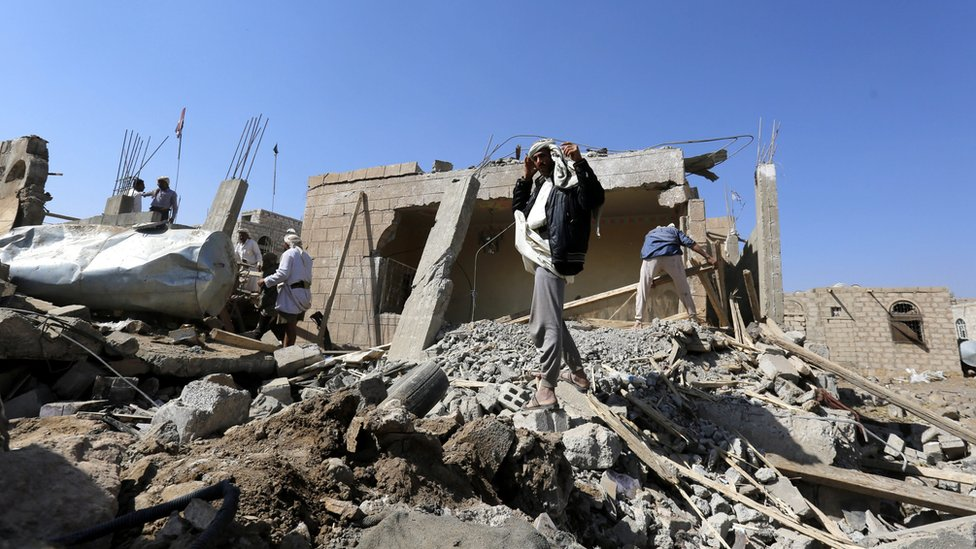 Yemenis stand over the rubble of destroyed houses
