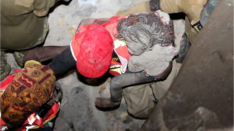 A young girl with ash-grey face, legs and hair is carried by a rescuer