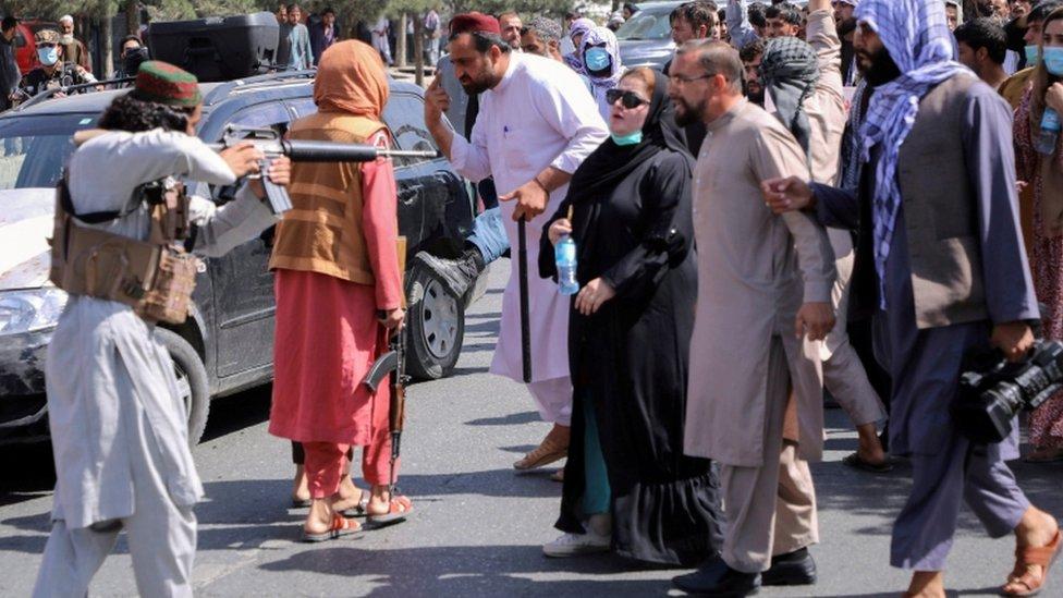 مقاتل من طالبان يوجه بندقيته نحو امرأة تشارك في تظاهرة في كابل