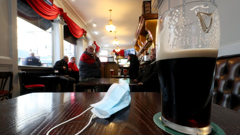 Pint of Guinness and face mask on pub table