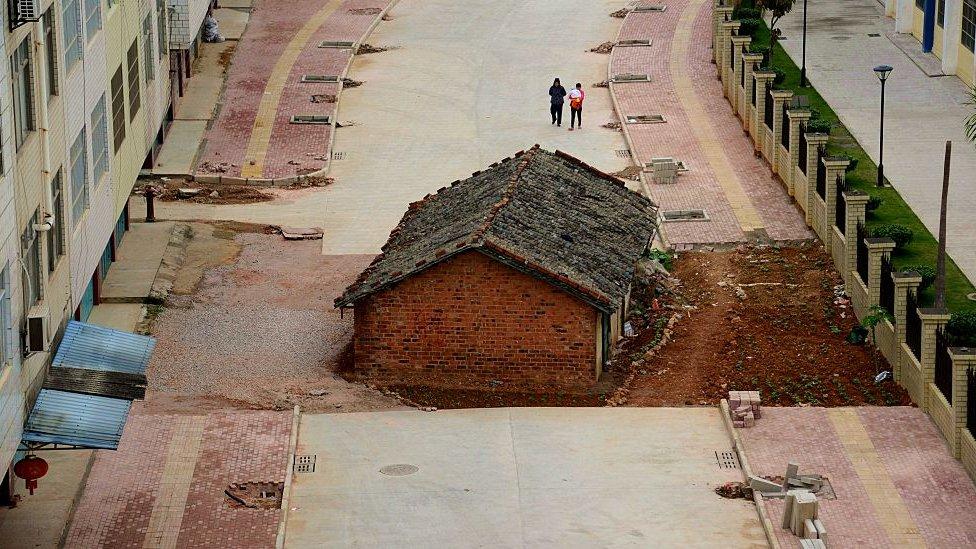 Rumah 'paku' memblokir jalan hampir seluruhnya di luar blok pemukiman pada 10 April 2015 di Nanning, Cina Selatan.