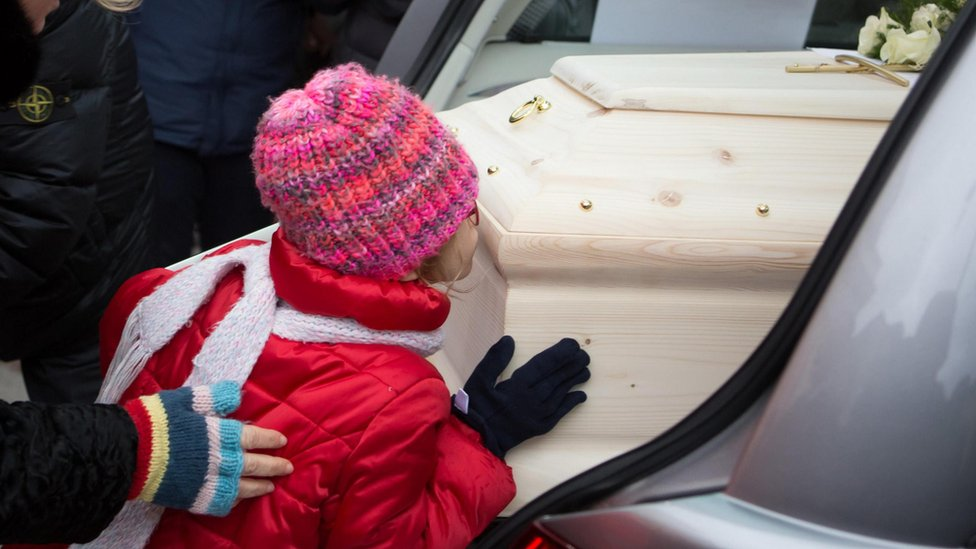 One of four children of Eleonora Girolimini kisses the coffin of her mother after the funeral Mass at the Senigallia Cathedral in Ancona, central Italy, 15 December 2018