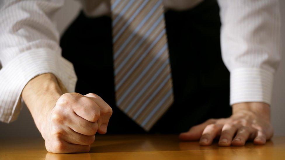 Un hombre con los puños cerrados en la mesa.