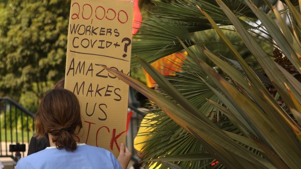 Woman with placard marching to Jeff Bezos' house