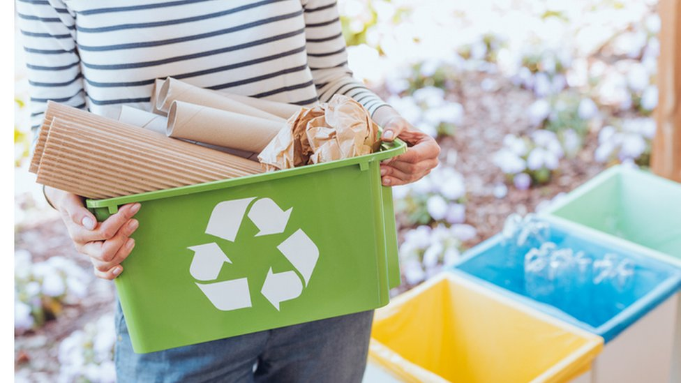 A stock image of a young woman sorting her paper waste for recycling