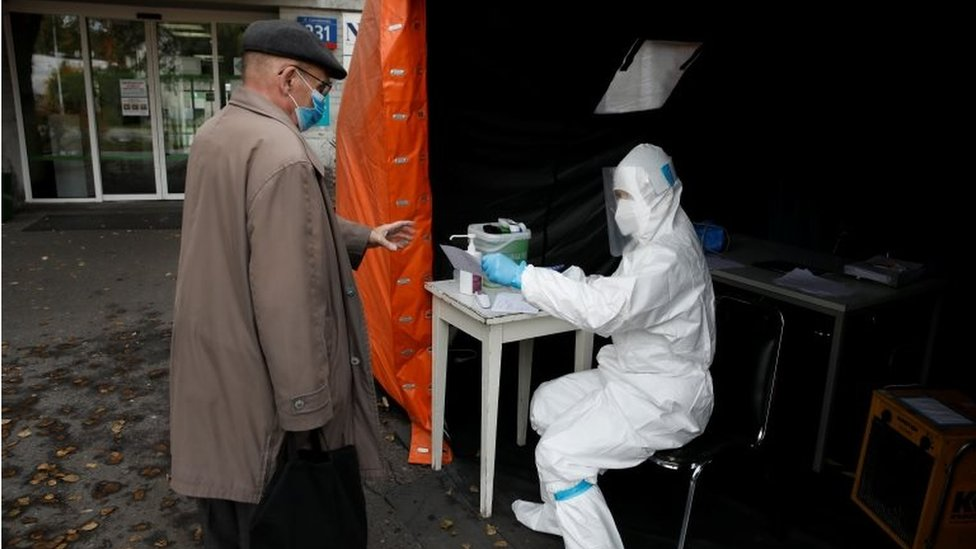 A health worker in protective suit gives a document to man, amid the coronavirus disease (COVID-19) outbreak, at a test centre in front of a hospital in Warsaw, Poland on 27 October 2020.