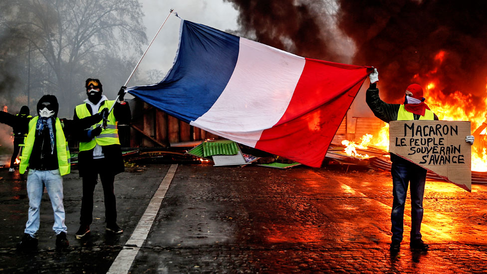 Protesters hold a French flag near a burning barricade in Paris during a protest of yellow vests