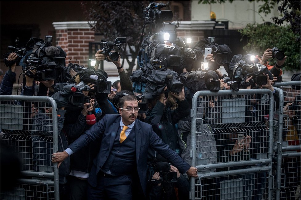 A crowd of cameramen try to get through a gate as a man holds them back