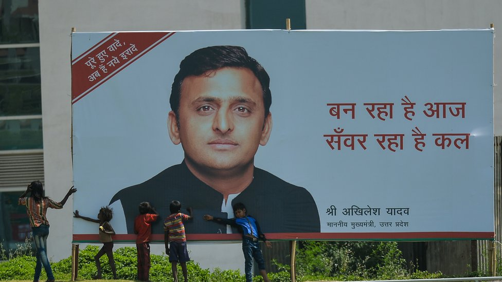 Young Indian children play around a hoarding featuring an image of Uttar Pradesh Chief Minister Akhilesh Yadav in Greater Noida on April 12, 2016.