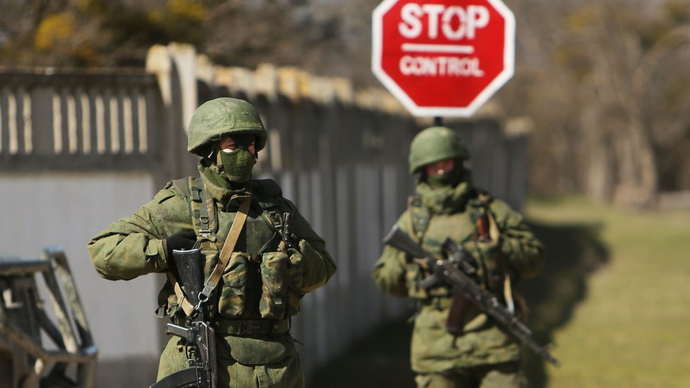 Armed soldiers without identifying insignia keep guard outside a Ukrainian military base in the town of Perevevalne near the Crimean city of Simferopol on March 17, 2014
