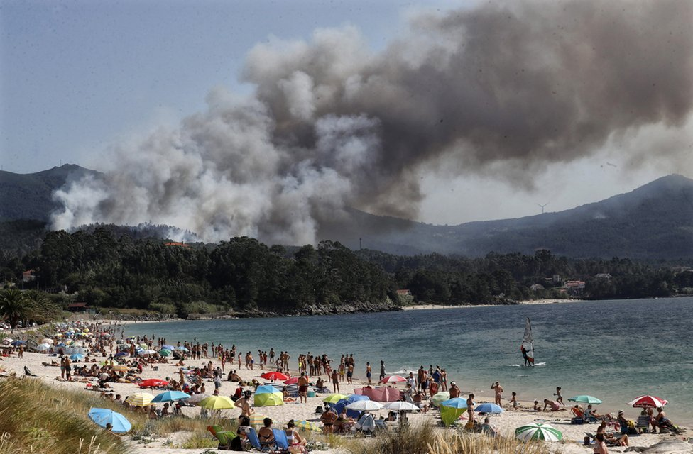Smoke rises from a forest fire near a tourist beach