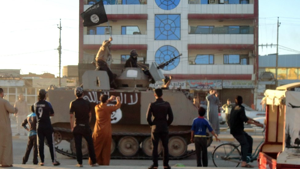 Iraqis stand watching as an armoured vehicle carrying armed militants holding up an Islamic jihadist flag drives past in Falluja on 20 March 2014