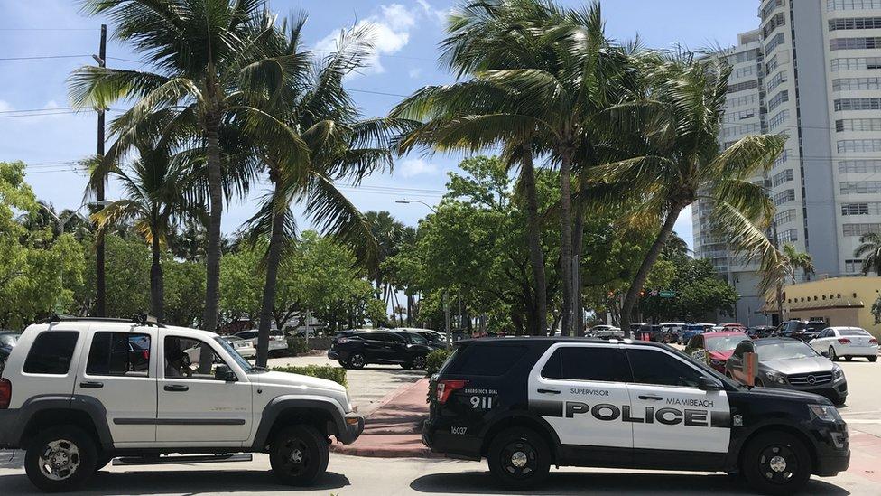 Auto de policía y un auto blanco detrás en Miami Beach