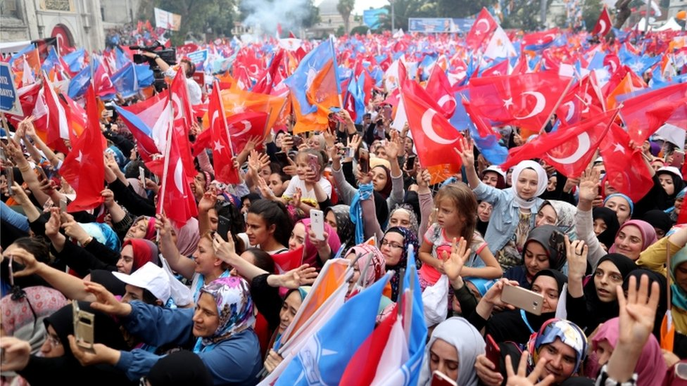 A dense crowd cheer and wave flags at a pro-Erdogan rally