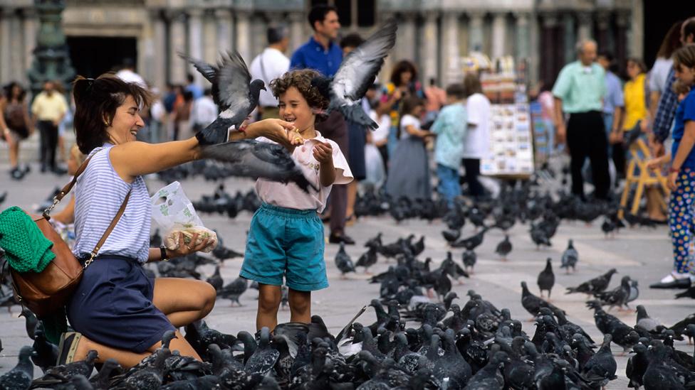 Mujere y su hijo dando de comer a palomas en una plaza