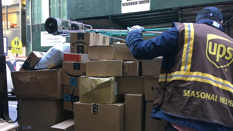 Seasonal help at UPS loads a dolly with boxes in New York