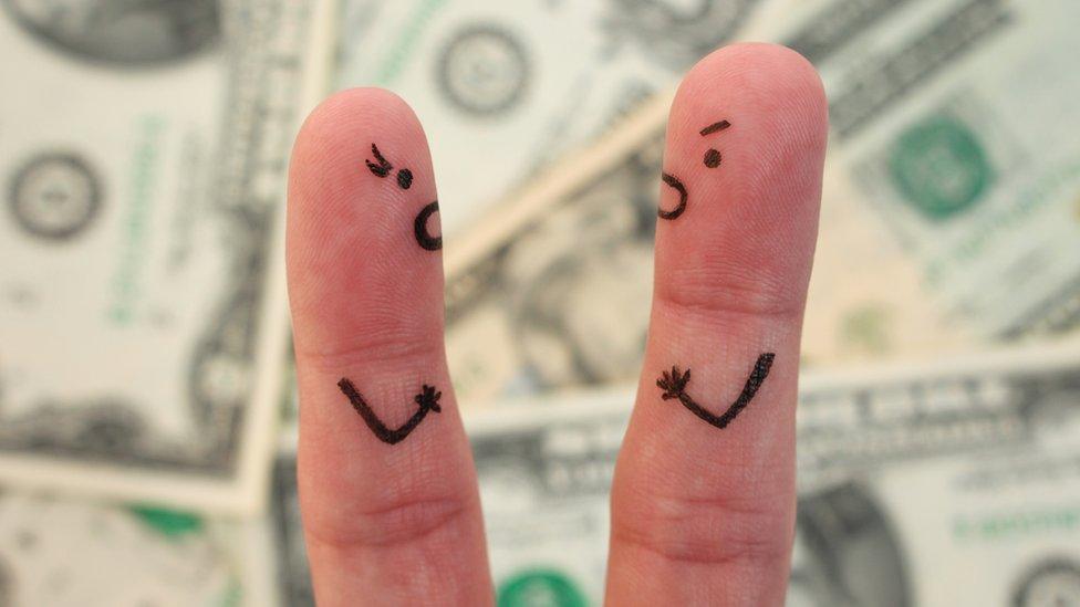 Dedos con caras de personas sobre billetes