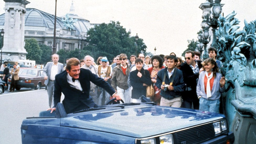 In this scene from the film of A View to a Kill, Roger Moore as Bond clambers out of a wrecked Renault car