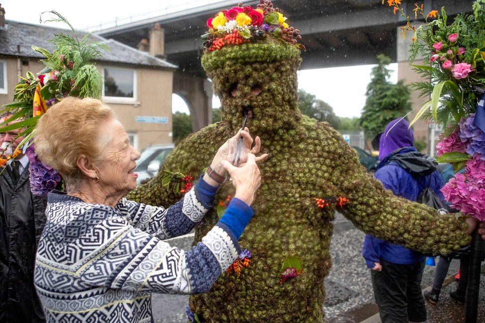Burryman Andrew Taylor is given whisky through a straw by local resident Mary Hamblin