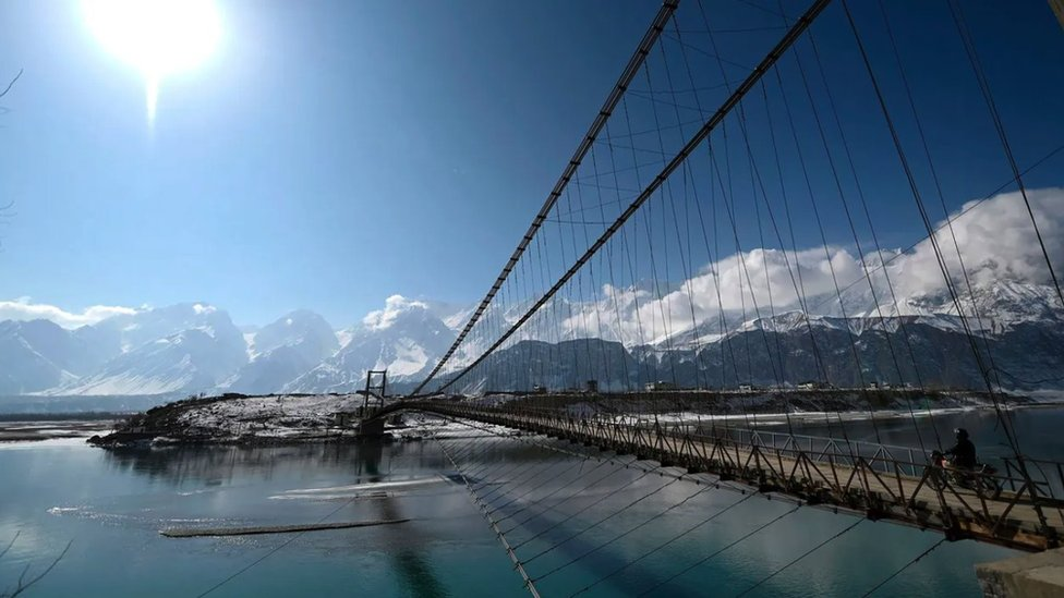A bridge over the Indus river with views of glaciers in the background