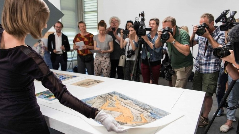 An official displays artwork during a press preview of the first masterpieces of the estate of Cornelius Gurlitt at the Museum of Fine Arts Bern (07 July 2017)