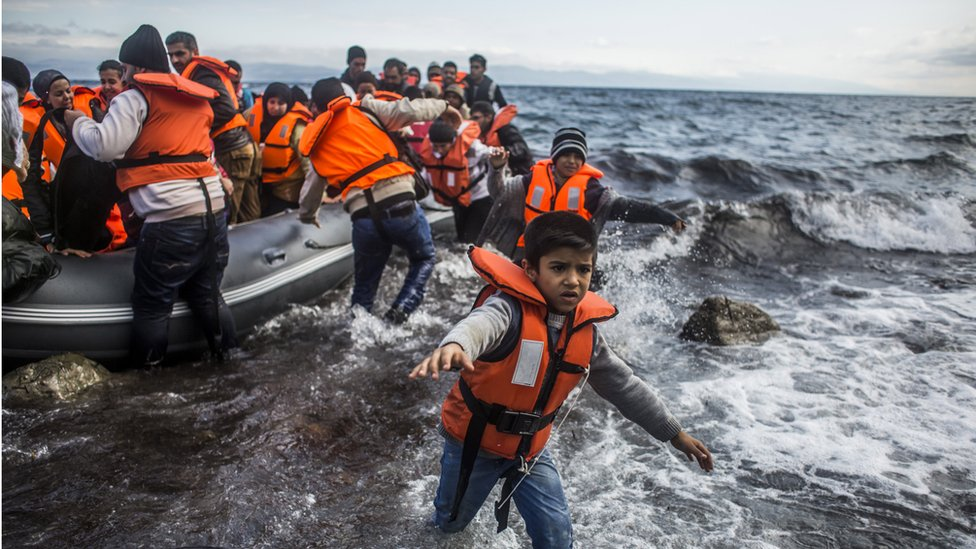Image shows refugees arriving on the shores of the Greek island of Lesbos in October 2015