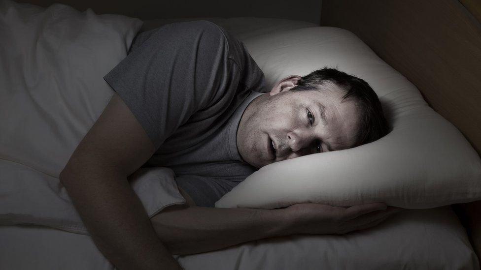Hombre en cama intentando dormir.