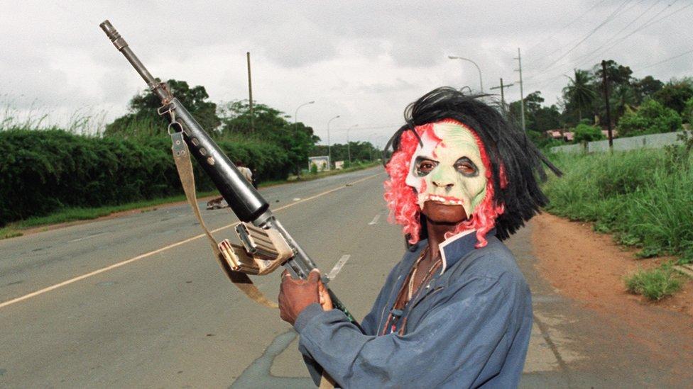 Un enmascarado rebelde leal al señor de la guerra Charles Taylor, del Frente Nacional Patriótico de Liberia, sostiene un arma mientras patrulla las calles de Monrovia en 1990.