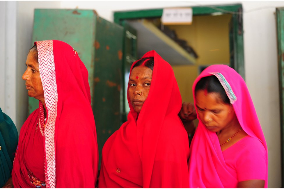 Indian women wait in a queue to cast their ballot at a polling station in Uttar Pradesh in 2014.