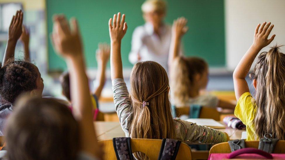 Crianças na sala de aula com as mãos erguidas