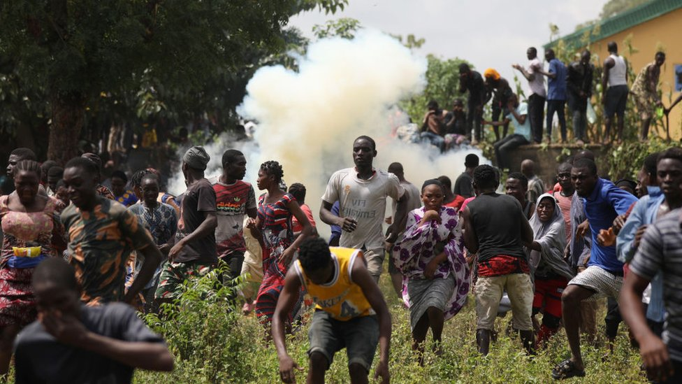 People run from a tear gas shot by Nigerian police officers during a mass looting of a warehouse that have COVID-19 food palliatives that were not given during lockdown to relieve people of hunger, in Abuja, Nigeria, on October 26, 2020.