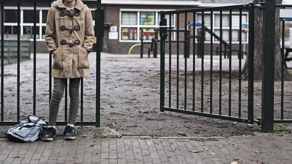 Child waiting at the school playground gates
