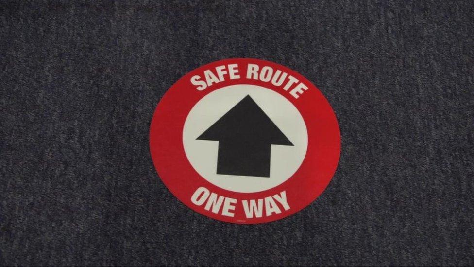 One way sign on corridor floor