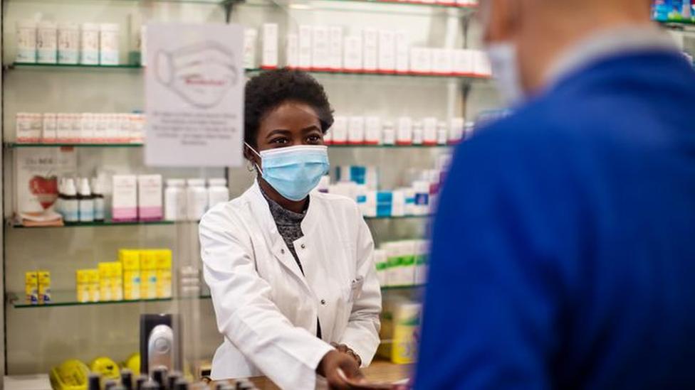 Farmacêutica atende cliente atrás do balcão de uma drogaria