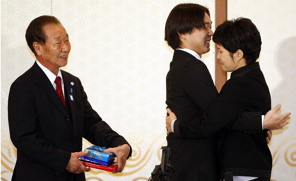 Shigeo Iizuka looks on as Koichiro Iizuka, son of the abductee Yaeko Taguchi, hugs former North Korean spy Kim Hyun-hui before a press conference on March 11, 2009 in Busan, South Korea.