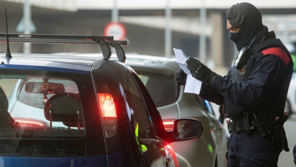 Un policía revisa documentos en un control en Cataluña.