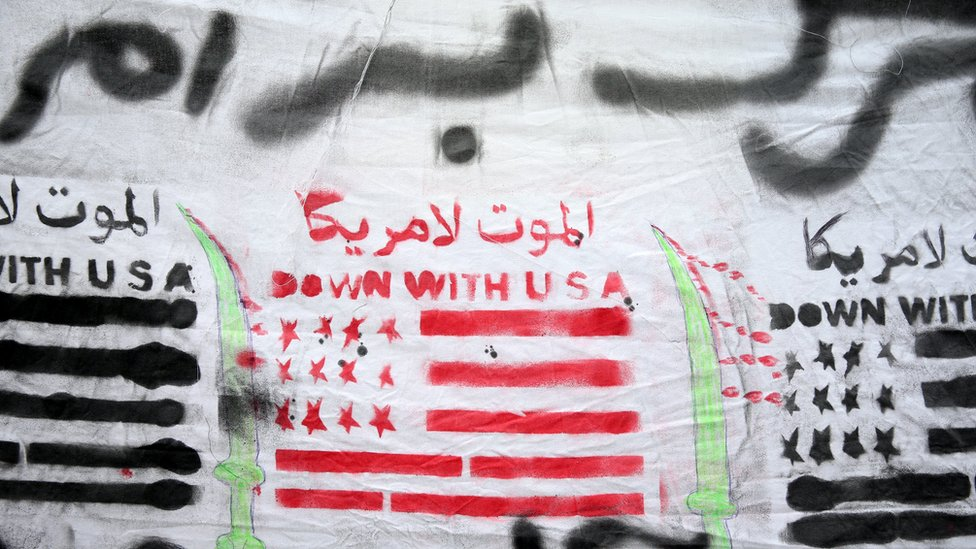 """A banner depicting a US flag and reading """"death to America and death to Al Saud"""" is carried by protesters at a rally after Friday prayers in Tehran, Iran (8 January 2016)"""
